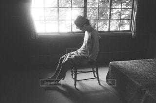 ウィンドウの横にあるベッドの上に座っている男の写真・画像素材[856030]