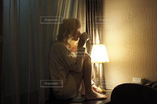 暗い部屋に座っている人の写真・画像素材[977846]