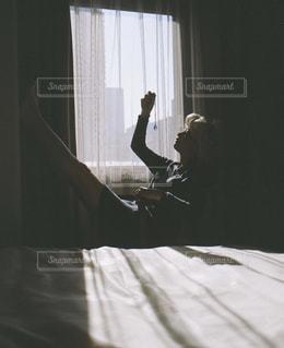 ウィンドウの横にあるベッドの上に座っている人の写真・画像素材[979321]