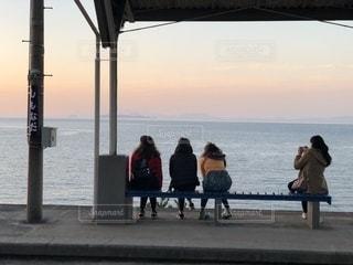 海を望むベンチに座っている人々 のグループの写真・画像素材[979678]
