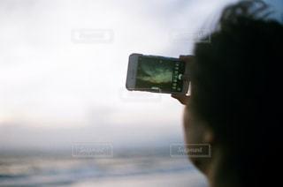 携帯で空を撮る女の子の写真・画像素材[1131676]