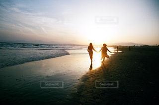 海の横にある砂浜のビーチの上に立っている人の写真・画像素材[1196365]