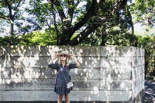 フェンスの横に立っている女性の写真・画像素材[1200672]
