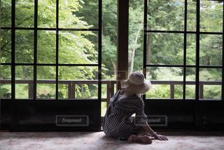 ウィンドウの横に座っている人の写真・画像素材[1298949]