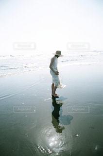波打ち際に立っている女の子の写真・画像素材[1320099]