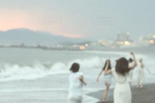 水の体の近くのビーチの上を歩く人々 のグループの写真・画像素材[1460284]