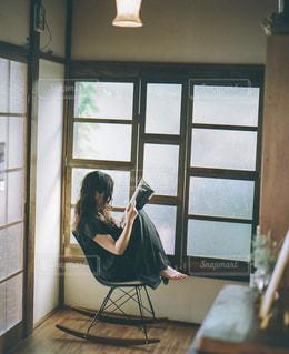 窓の前に座っている人の写真・画像素材[1721081]
