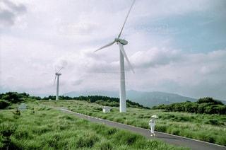 緑豊かな野原の上の風車の写真・画像素材[2367405]