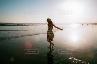 水辺のビーチを歩いている女の子の写真・画像素材[2695373]