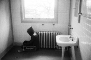 窓の下に座っている男性の写真・画像素材[2798814]