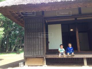 建物の前にあるベンチに座っている子どもたちの写真・画像素材[761631]