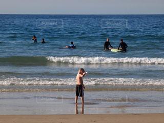 海の横にあるビーチの上を歩く人々 のグループの写真・画像素材[1091100]