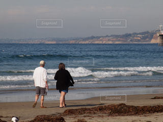 老夫婦 老後 セカンドライフ 終活 年金 / 海の横にあるビーチの上を歩く人の写真・画像素材[1091103]