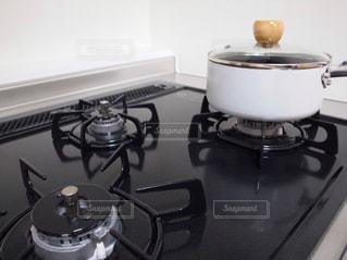 黒いガスコンロと白い片手鍋の写真・画像素材[1131651]