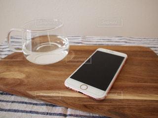木製テーブルの上の携帯電話 スマートフォン スマホの写真・画像素材[1131653]