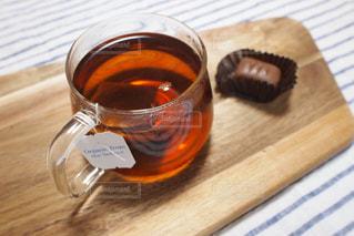 木製テーブルの上のガラスのコップに注いだ紅茶とチョコレートでリラックスタイムの写真・画像素材[1131654]