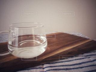 木目調のカッティングボードのうえに耐熱グラスに注いだお白湯の写真・画像素材[1131655]
