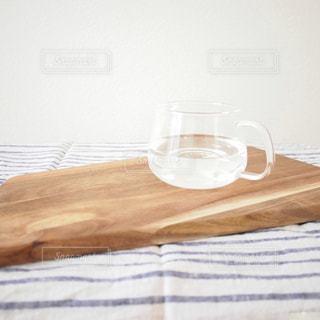 木製のテーブルの上に耐熱ガラスに注いだお白湯 - No.1131656