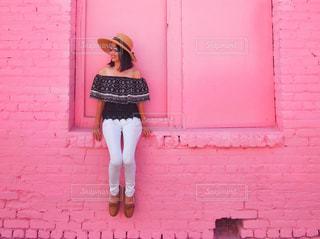 ピンクの壁のまえに座っている女の子の写真・画像素材[1132112]