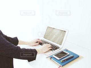ノート パソコンの前に座っている人 女性 20代 30代 OL ビジネス 仕事 タイピング 入力の写真・画像素材[1207693]