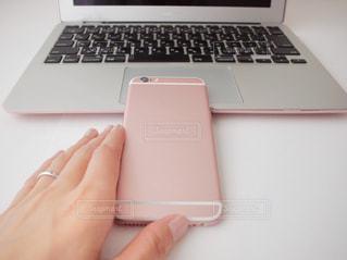 テーブルの上 ラップトップ コンピューター ノート パソコン スマホ 手 ピンクの写真・画像素材[1212273]