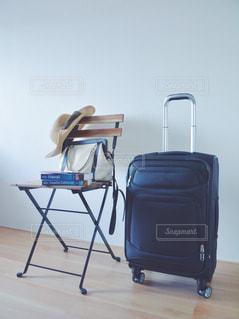 木製の椅子の上に座って荷物のバッグ スーツケース パスポート スマホの写真・画像素材[1272591]