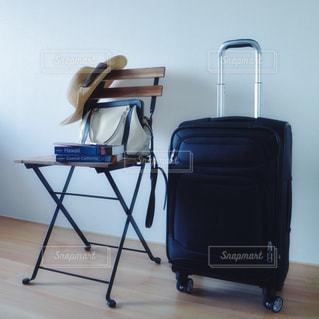 キャリーケース スーツケース パスポート スマホ トラベル 海外 旅行 / 木製の椅子の上に座って荷物のバッグの写真・画像素材[1272625]