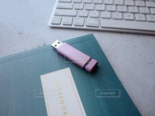 置き画 PC キーボード USBメモリ ノートブック メモ帳 女性 ピンク エメラルド グリーンの写真・画像素材[1273968]