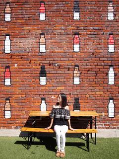 れんが造りの建物の前にあるベンチに座っている人 女性 20代 30代 海外 LAの写真・画像素材[1411857]