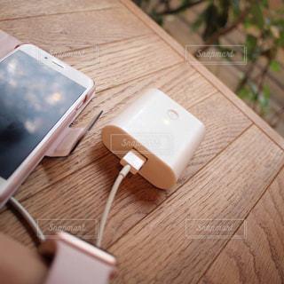 スマホ モバイルバッテリー ケーブル 充電中 木製のテーブルの上の写真・画像素材[1514430]