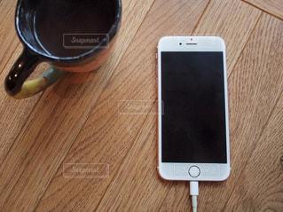 木製テーブルの上に座っているコンピューター スマホ スマートフォン ケーブル 充電中の写真・画像素材[1514433]
