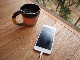 スマホ ケーブル 置き画 木製のテーブルの上に座ってコーヒー カップの写真・画像素材[1514446]