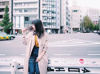 車の横に道を歩いている女性 20代 モデル ロングヘア 秋ファッションの写真・画像素材[1549535]