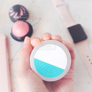 プラスチック製の容器を持っている手 スキンバーム リップ ピンクの写真・画像素材[1621730]