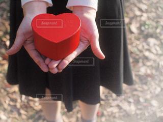赤のハートの箱を持っている女の子の手の写真・画像素材[1672234]