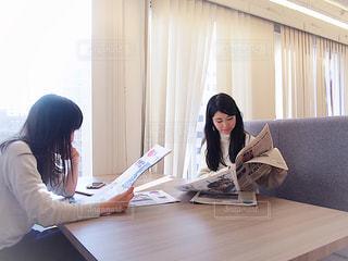 ラップトップを使用してテーブルに座っている女性の写真・画像素材[1821801]