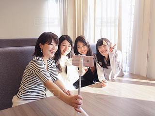 カメラにポーズのテーブルに座っている女性の写真・画像素材[1830022]