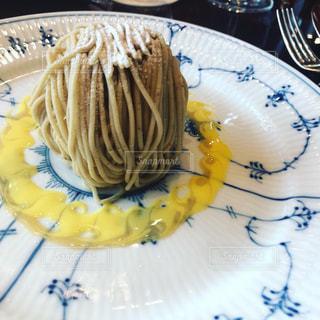 テーブルの上のケーキをのせた白プレートの写真・画像素材[1258445]