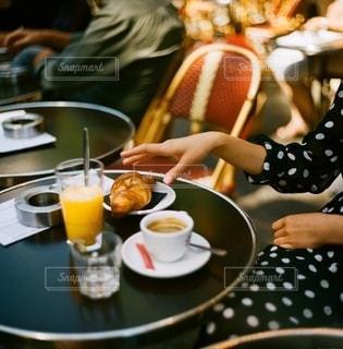 食べ物を食べるテーブルに座っている女性の写真・画像素材[2723369]