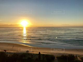 海の横にあるビーチに沈む夕日の写真・画像素材[1700688]
