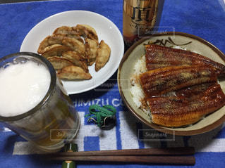 食品とテーブルの上のビールのカップのプレートの写真・画像素材[1055120]
