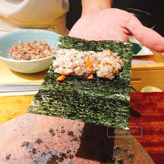 ブロッコリーと食品のプレートをテーブルに座っている女性の写真・画像素材[1830344]