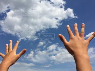 青い曇り空の女性の写真・画像素材[715782]