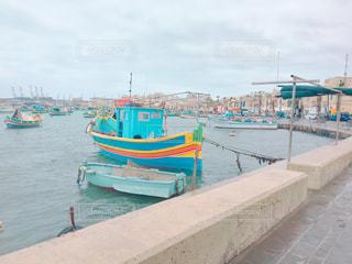水の体の横にドックに座っているボートの写真・画像素材[1409550]