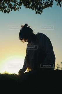 夕焼けの前に立っている女性の写真・画像素材[2687030]