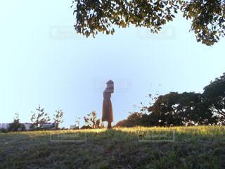木々を背景に草原に立つ女性の写真・画像素材[2687384]