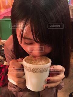 コーヒーを飲みながらテーブルに座っている人の写真・画像素材[2812281]