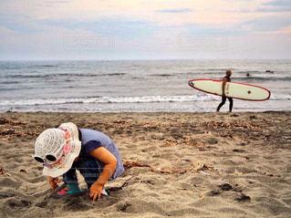 ビーチでサーフボードを運ぶ男 - No.765949