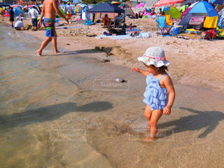 ビーチの砂の上に立っている小さな男の子の写真・画像素材[766015]