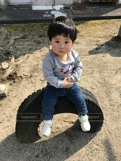 タイヤの上に座る男の子の写真・画像素材[1098597]